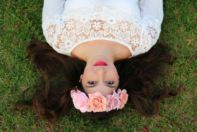 Lindo look de uma garota deitada na grama, usando coroa de flores
